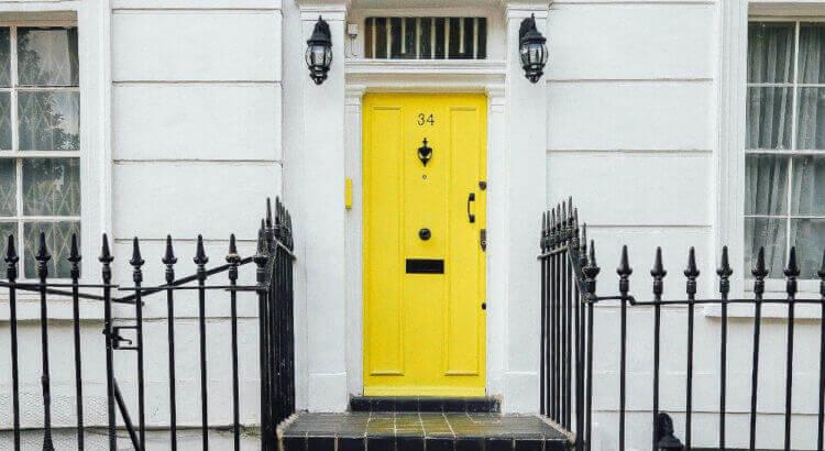 Жълта входна врата с ограда