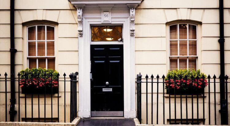 Черна врата с прозорци и цветя